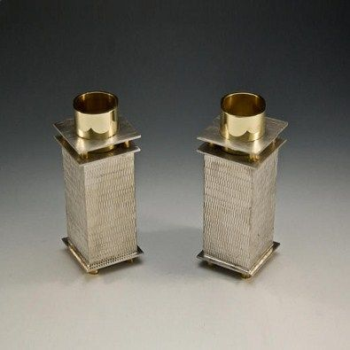 Joy Stember Stone Texture candlestick holders. They are fabricated from pewter and brass and fit a standard sized tapered candle. The texture is roll printed using a rolling mill. Finished with brass footings and done in a rectangular design. Comes artist signed.