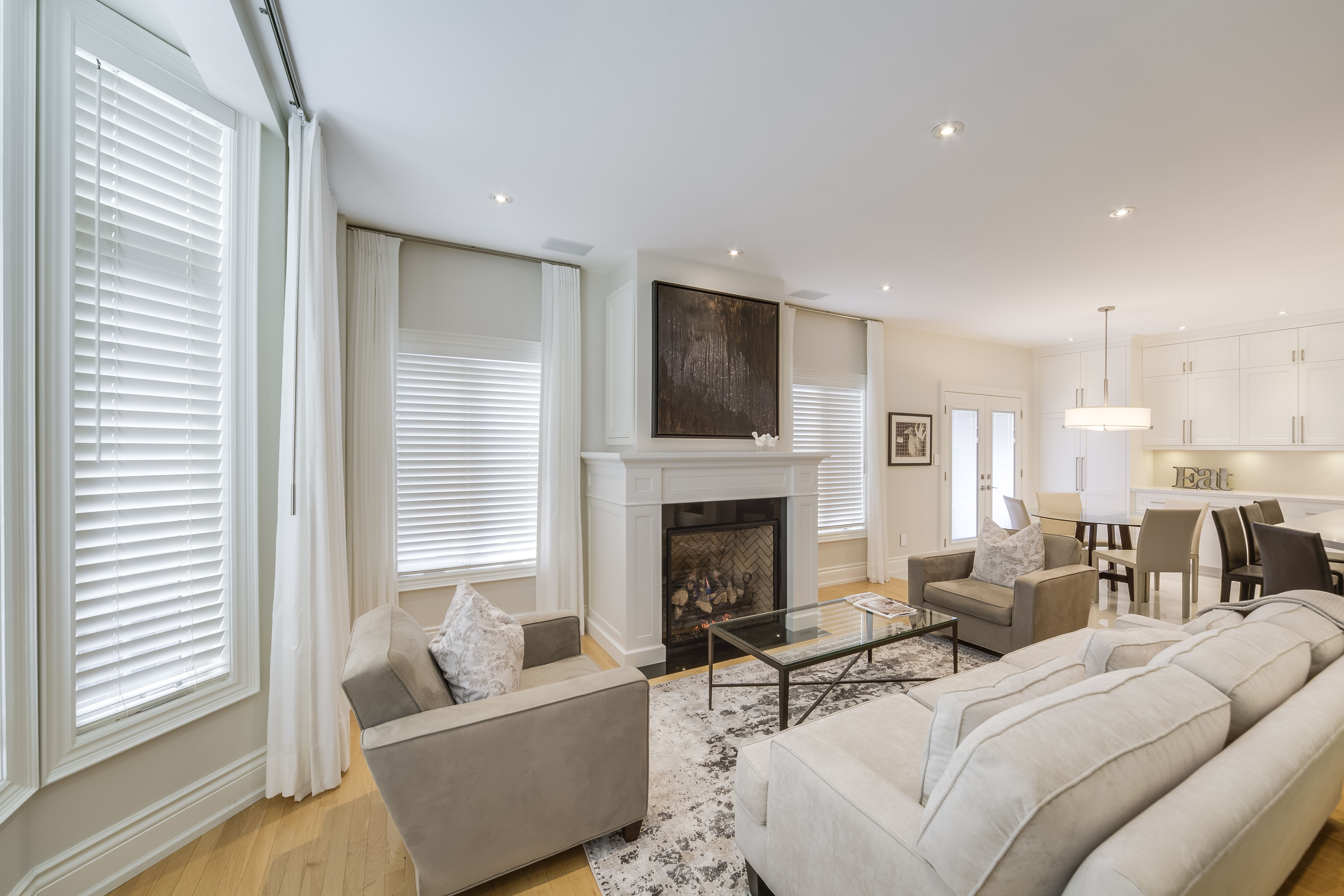All White Window Coverings Such As Wood Blinds And Linen Drapes Bring A Light And Chic Vibe To This Cozy Condo Blinds For Windows Wood Blinds Budget Blinds #wooden #blinds #for #living #room