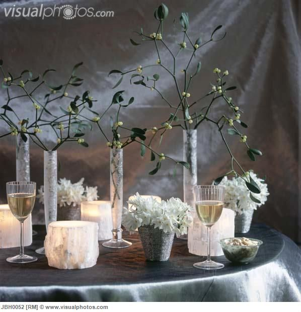 White Christmas party decorations with mistletoe and frosted glass candle holders on silver tablecloth