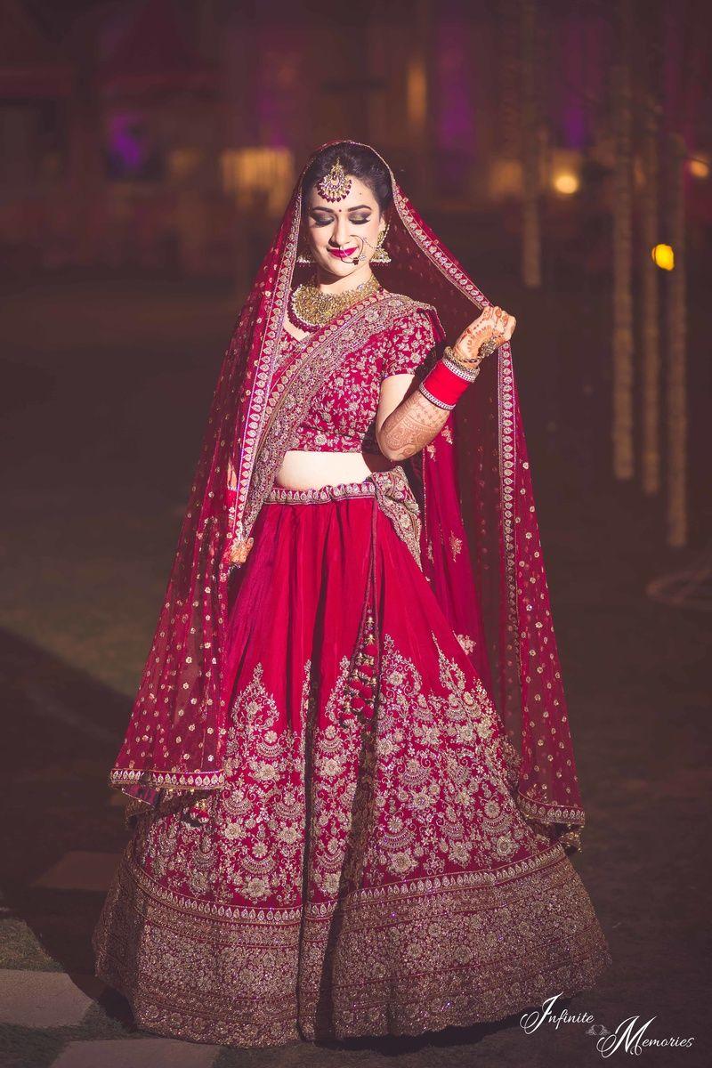 Bride In Deep Red Bridal Lehenga Holding Dupatta Designer Bridal