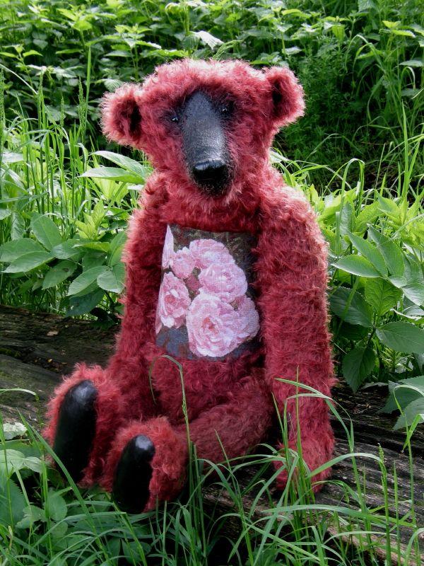 Der Bär mit roten Rosen . Das Bild ist gestickt . An der Pferdekoppel