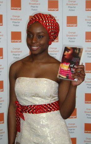 desfemmesetdeslivres: Chimamanda Ngozi Adichie holding her novel Half of a Yellow Sun.