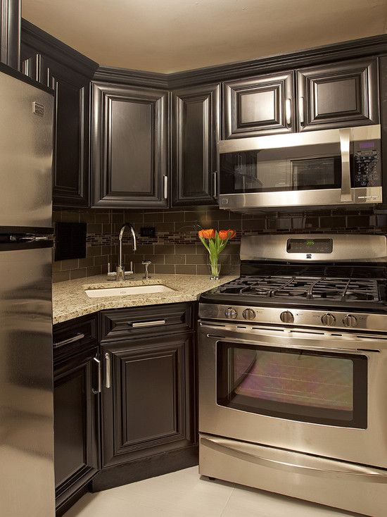 Black Cabinets, Stainless Steal Appliances, Light Gray Or Charcoal Colored  Counter Tops, Light Gray Painted Walls.