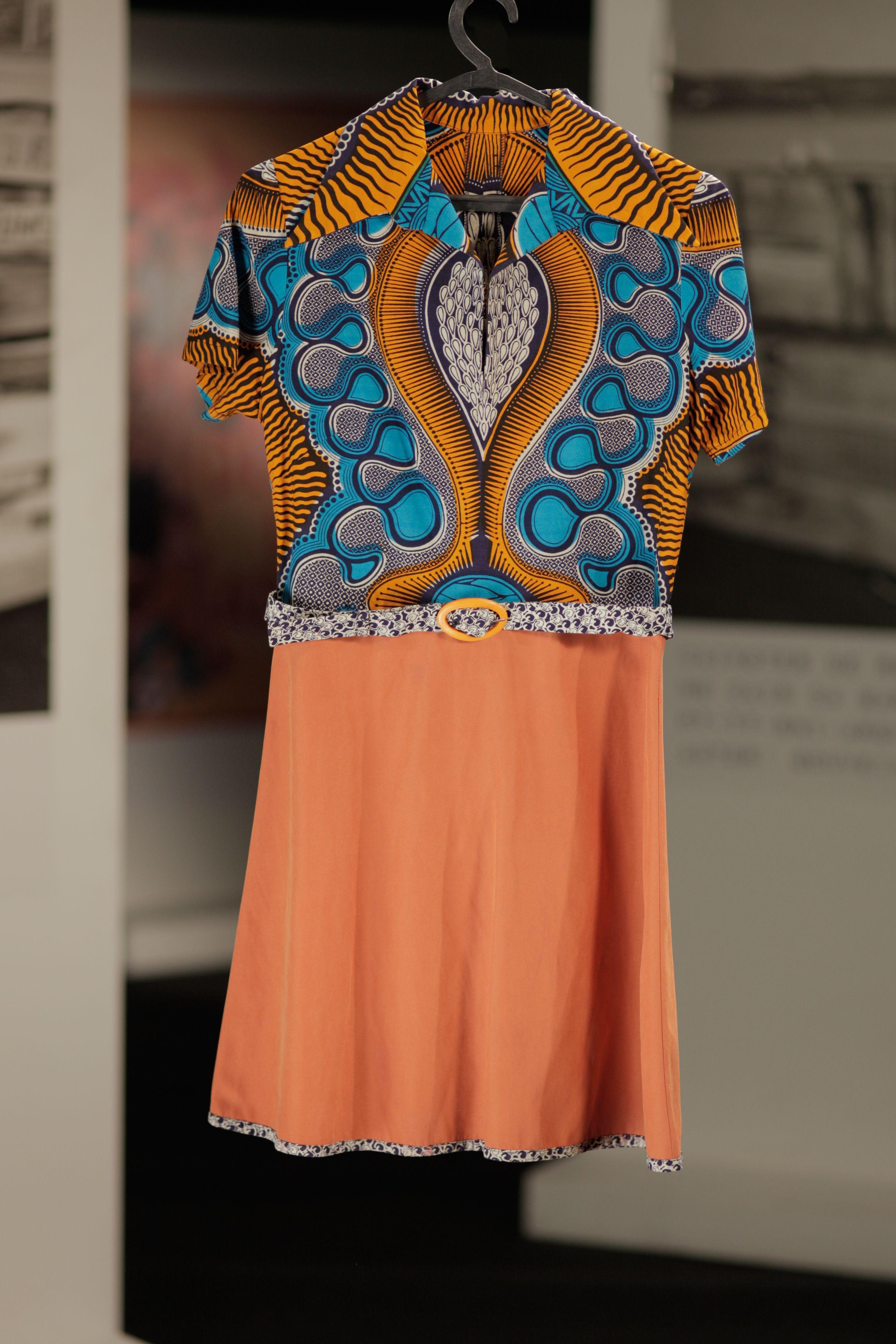Vestido laranja com padrão azul e formas geométricas africanas, cintado, de Ana Maria na série Depois do Adeus