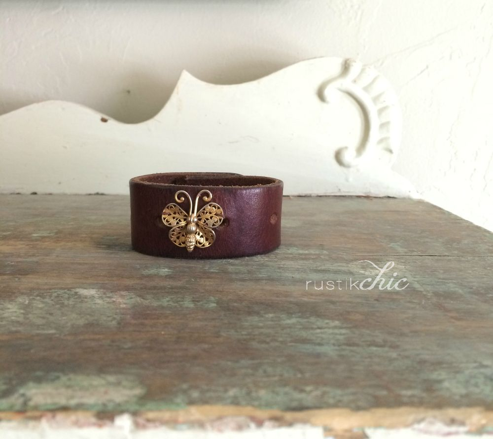 """Rustik Chic Upcycled One of a Kind Leather Cuff Bracelet From RustikChicDesigns A touch of Rustik, a touch of Chic... Upcycled from a perfectly vintage leather belt, this one of kind cuff is perfectly sweet. The ornate vintage butterfly brooch perfectly contrasts the worn vintage leather. Finished with a sturdy snap closure, should fit wrists up to 7.25""""Vintage and second hand items have charm and a history...What story will yours tell"""