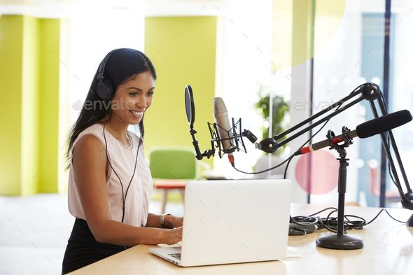 Young mixed race woman recording a podcast in a studio by monkeybusiness Young mixed race woman recording a podcast in a studio