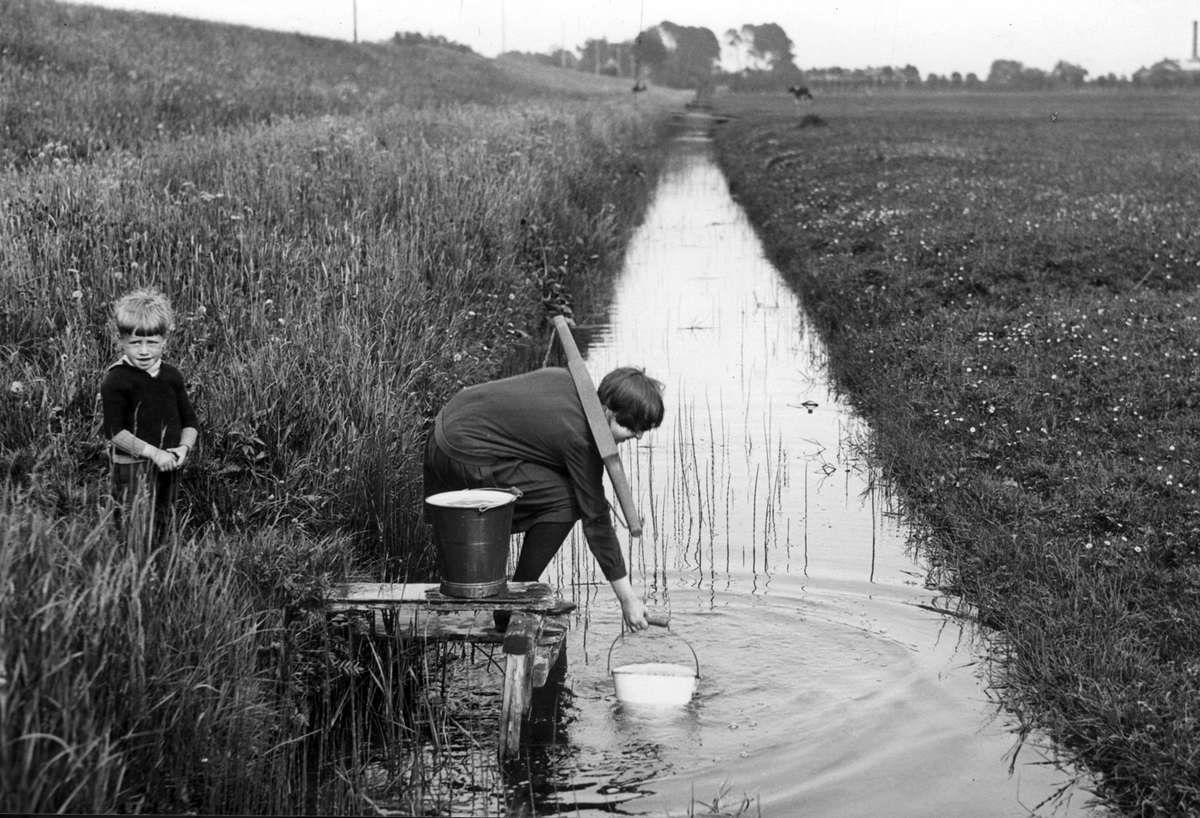 Watervoorzieningen. Jongetje en meisje (vrouw?) met juk halen met emmers drinkwater uit een sloot in het Land van Altena, 1931. Nederland. Serie fotos.