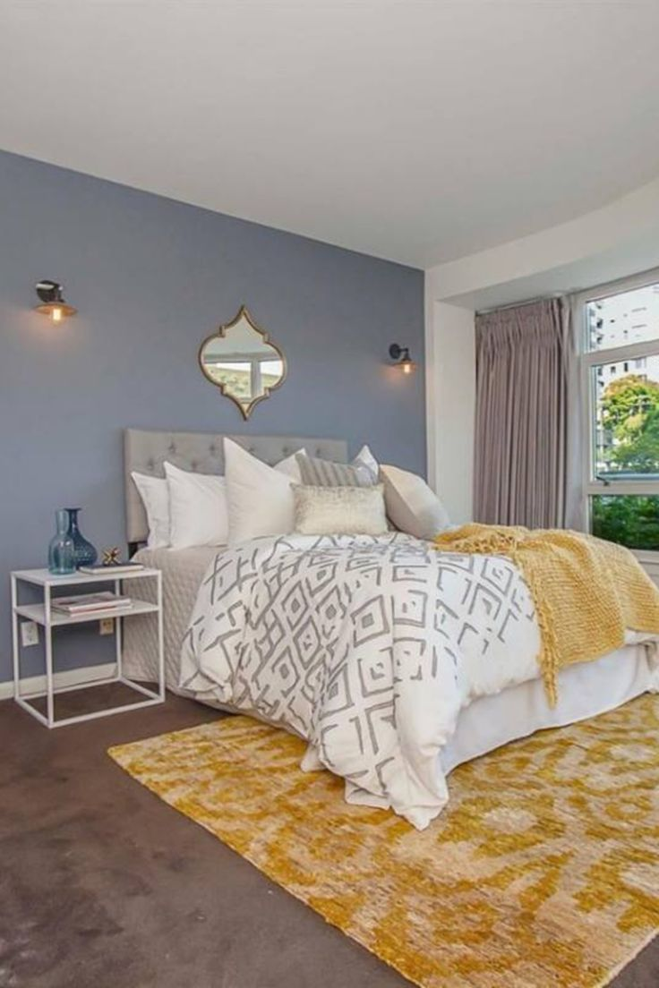 Classic #bedroom #with #blue #grey #accent #wall #and #yellow #rug #graybedroomwithpopofcolor