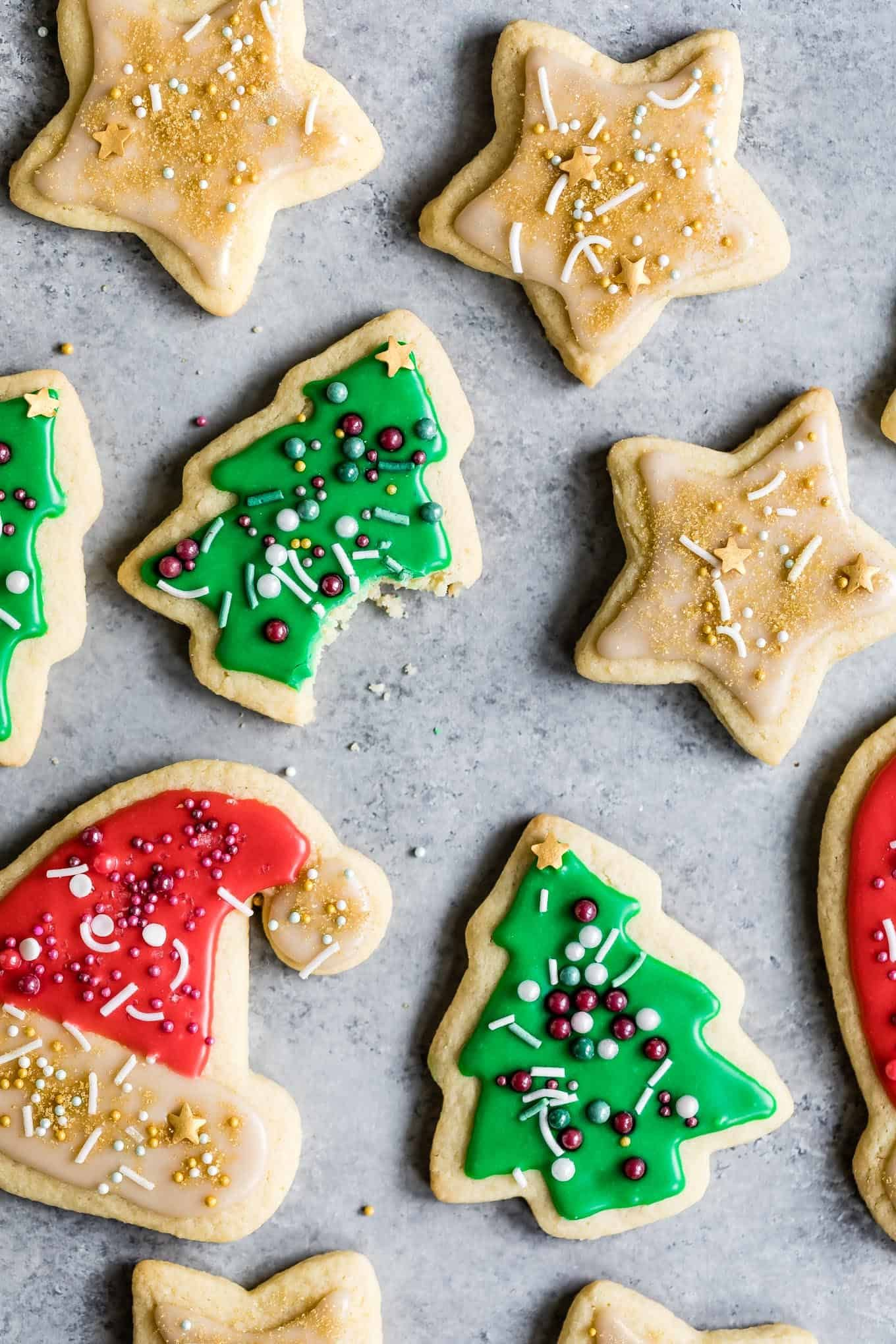 These soft cut-out gluten-free sugar cookies are decorated with super easy icing and festive sprinkles. They're the perfect gluten-free holiday cookie to leave out for Santa! #sugarcookies #glutenfree #cookies #icing #holiday #christmas #christmascookies #recipe #glutenfreecookies #easy #almond #cutout #cutoutsugarcookies