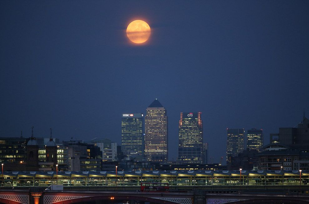 The blinking light at the top of One Canary Wharf is insignificant compared to the light from the supermoon. | 11 Mesmerising Photos Of The Harvest Supermoon Above The Skies Of Britain