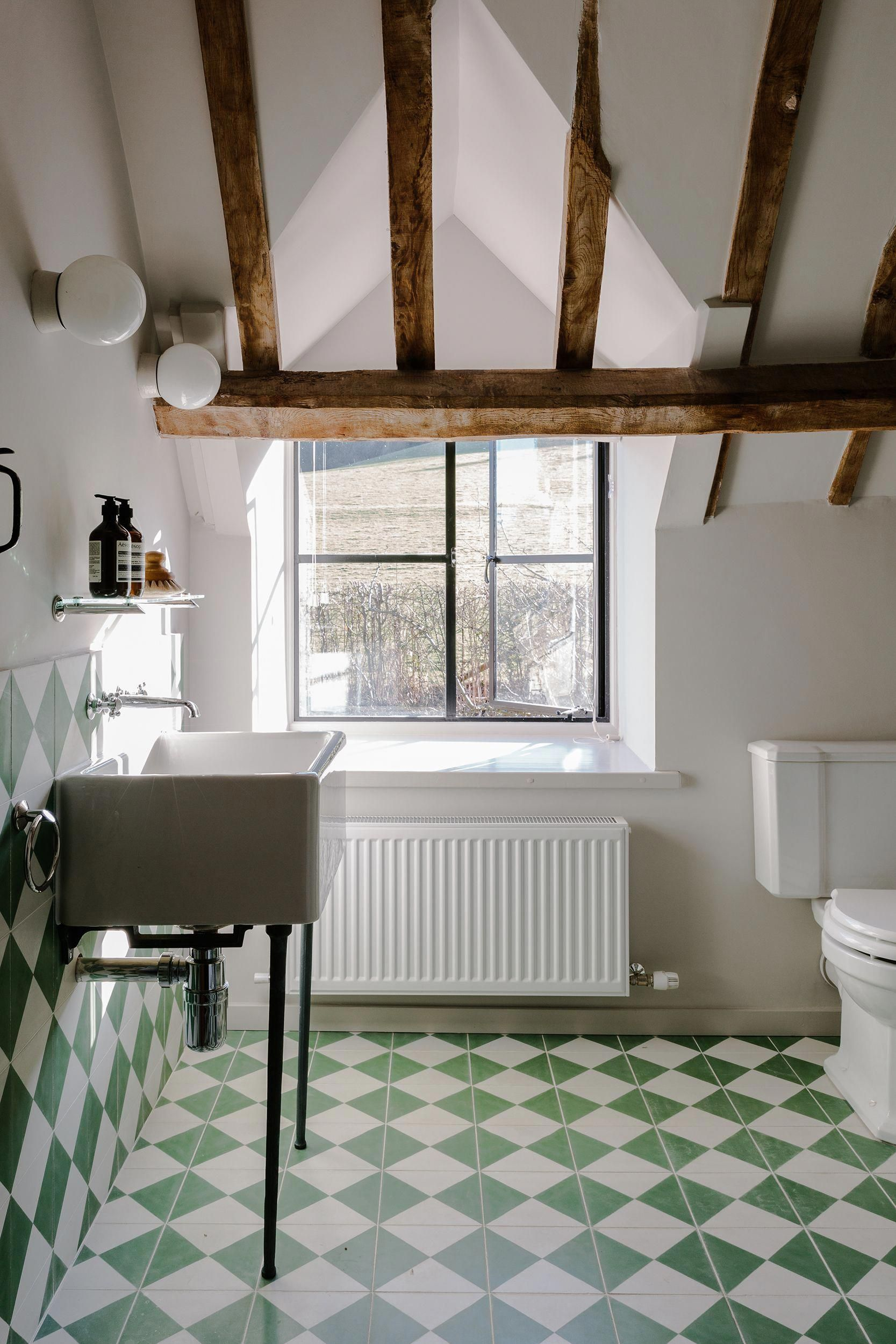 Beautiful country bathroom by Cotswoldfarmhideaway using Bert & May green churriana tiles, framed with rustic wood and decorated with understated white bathroom accessories. Credit: Photographer_ @_marinadenisova_Lighting_ @trainspotters.co.uk #bertandmay #tiles #countrybathroom #bathroom #rustic #wood #whitebathroom