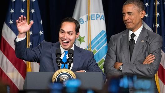 Julian Castro, secretary of U.S. Housing and Urban Development (HUD), center, gestures to employees as he and U.S President Barack Obama arrive to speak at the Department of Housing and Urban Development in Washington, D.C.