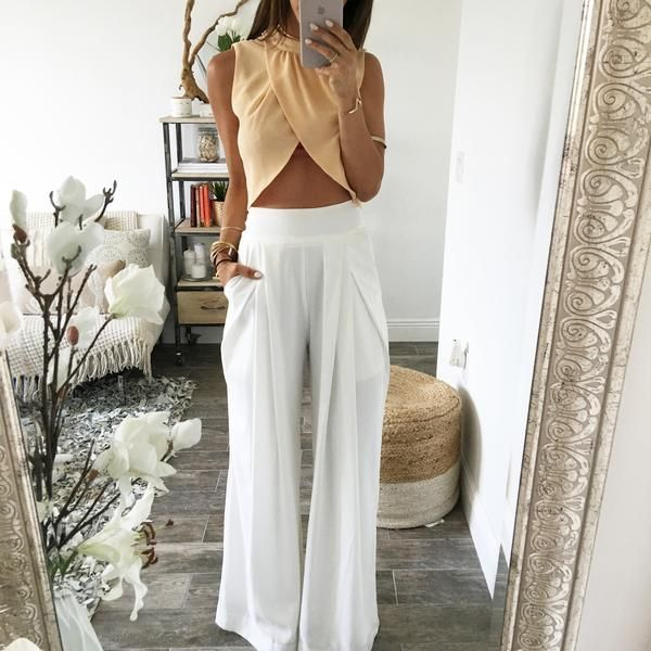 Wide leg, pleated white trousers. Zipper closure. Model is wearing Small. 100% Polyester