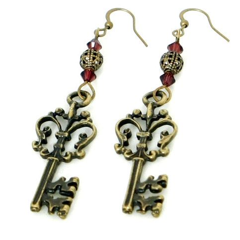 a92353d13198 These pretty steampunk earrings feature an ornate antiqued brass skeleton  key charm with round filigree beads and sparkling burgundy Swarovski crystal  ...
