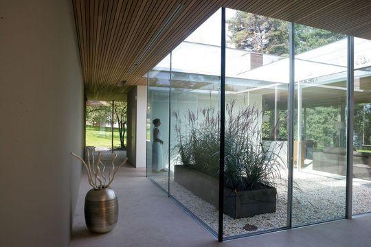 Au bord du lac une maison en verre entourée de verdure esprit zen pour
