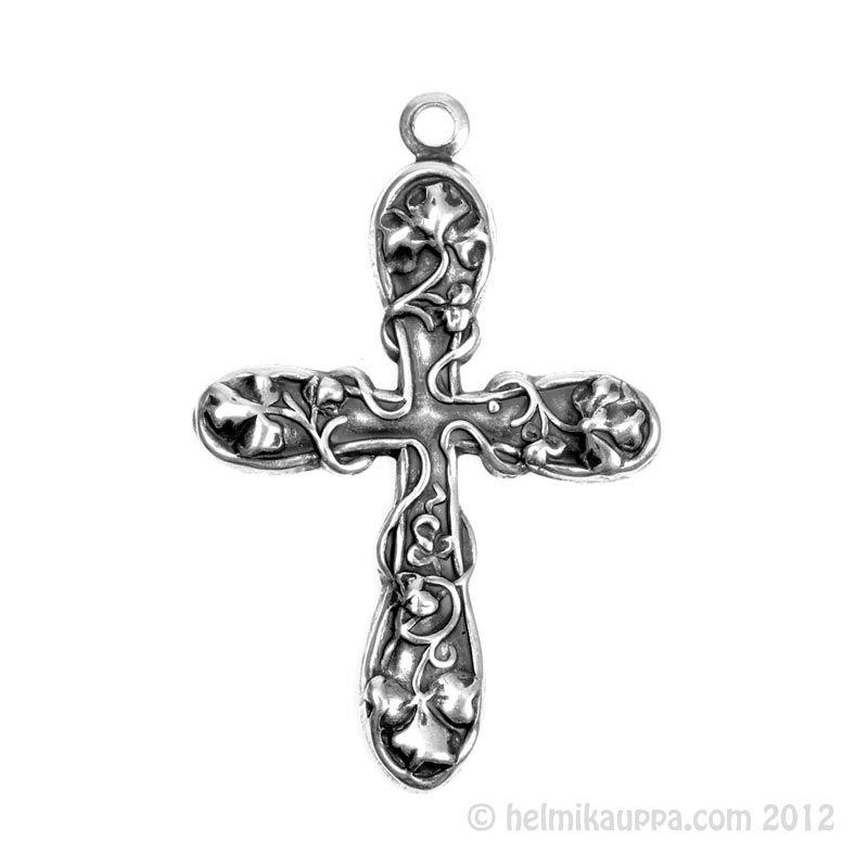 Kukkaköynnöksin koristeltu kaunis risti. Päällystetty aidolla hopealla.