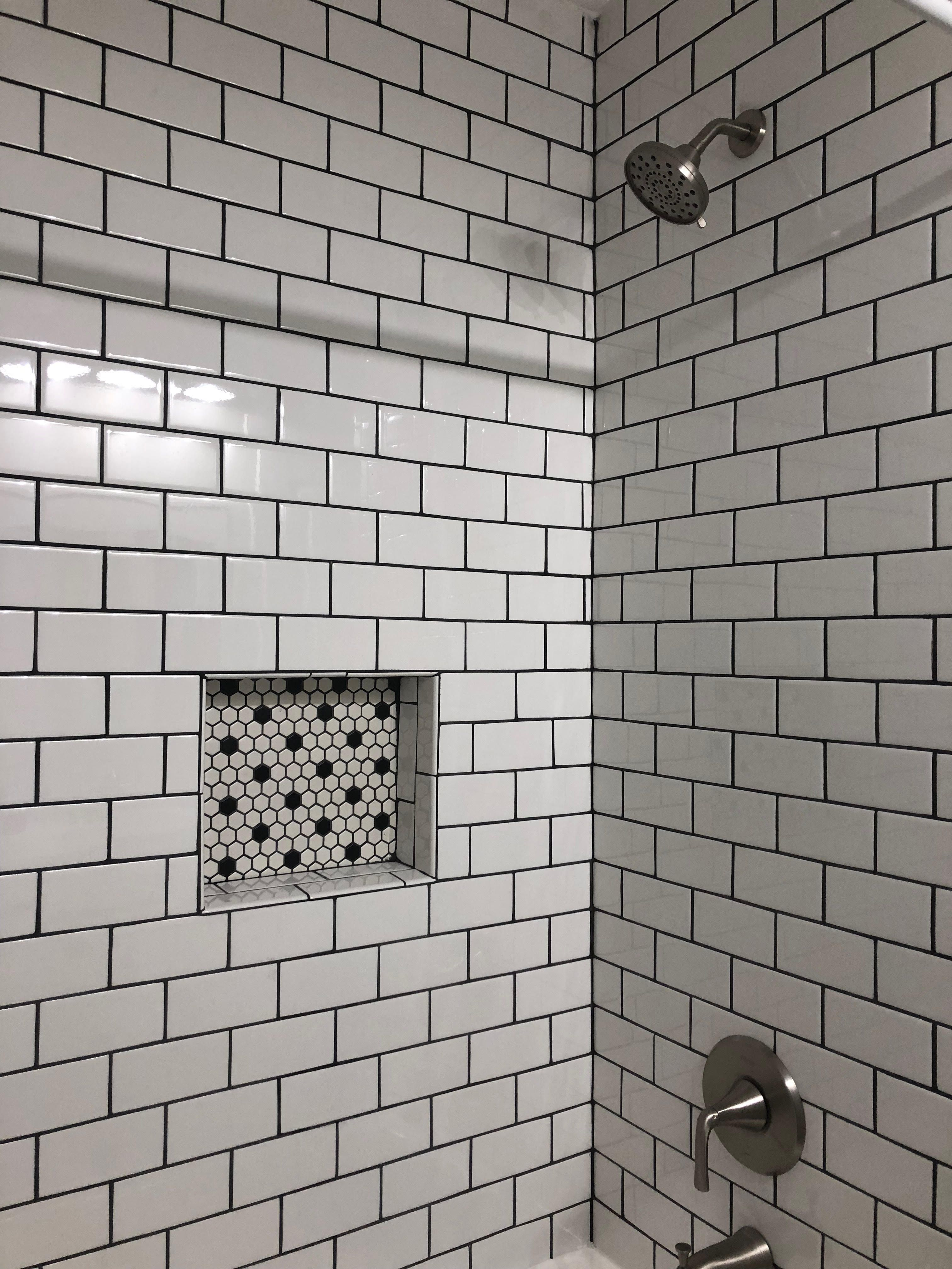 Guest Bath Reno With White Subway Tile Dark Gray Grout Honeycomb Black And White Mosaic Tiles Pfister Bru Black Tile Bathrooms White Tile Shower Shower Tile