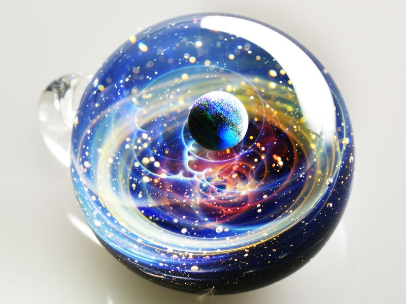 L'artiste japonais Satoshi Tomizu crée dans des sphères de verre des petits univers colorés composés de planètes, de lunes et d'étoiles grâce à des opales, des paillettes d'or et du verre coloré.