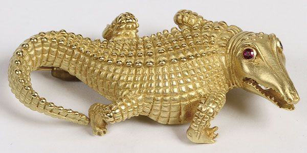 "A VAHE NALTCHAYAN DESIGNER GOLD ALLIGATOR PIN, 1990. Well sculpted and set with ruby eyes, stamped ""VAHE NALTCHAYAN 1990 18K USA"" Length 2.375 inches (6 cm), weight 41 grams."