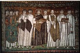Mosaico Giustiniano e il suo seguito della Basilica di San Vitale. Giustiniano indossa un manto color porpora, simbolo dell'imperatore, alle orecchie ha tre pensagli (che simboleggiano la trinità), ai piedi le pantofole imperiali. L'espressione è anonima e al suo fianco si trova Massimiano, che rappresenta l'ultimo viso con le caratteristiche tipiche del ritratto romano.
