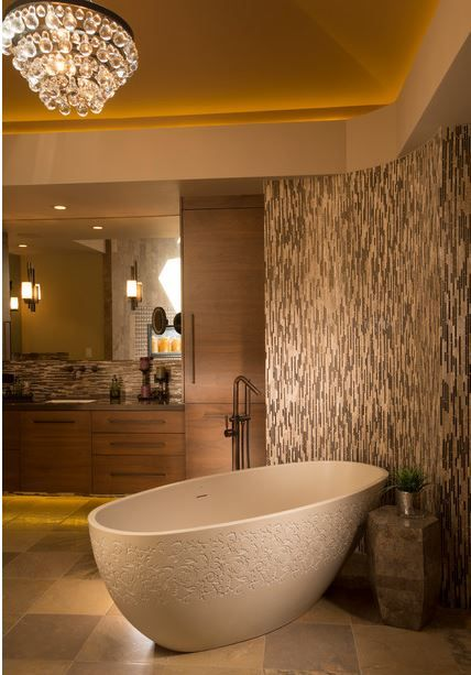 An engraved tub is nestled into the curved wall of tile -- quiet repose.