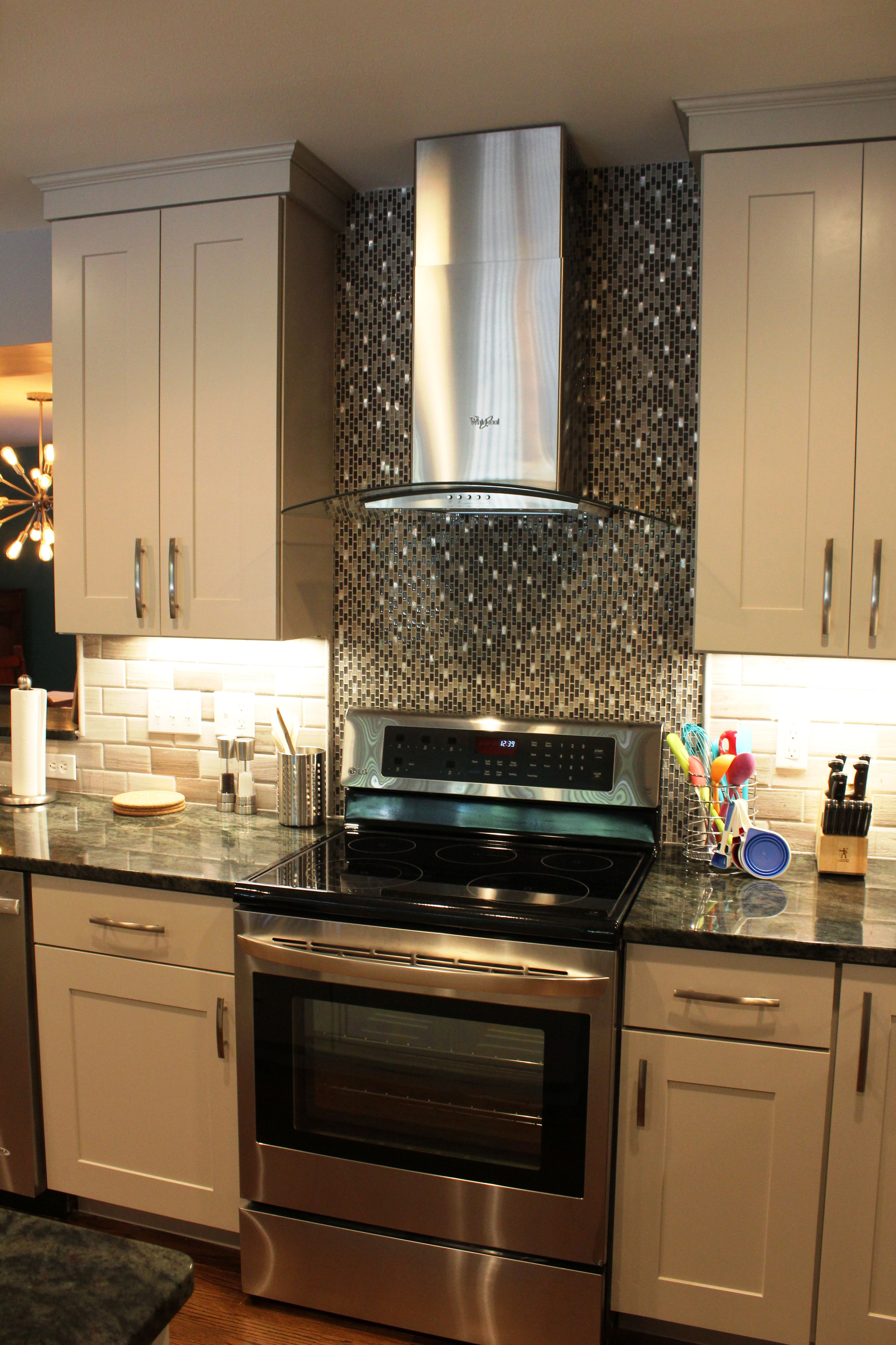 White shaker cabinets subway tile mosaic accents the stainless and glass hood also