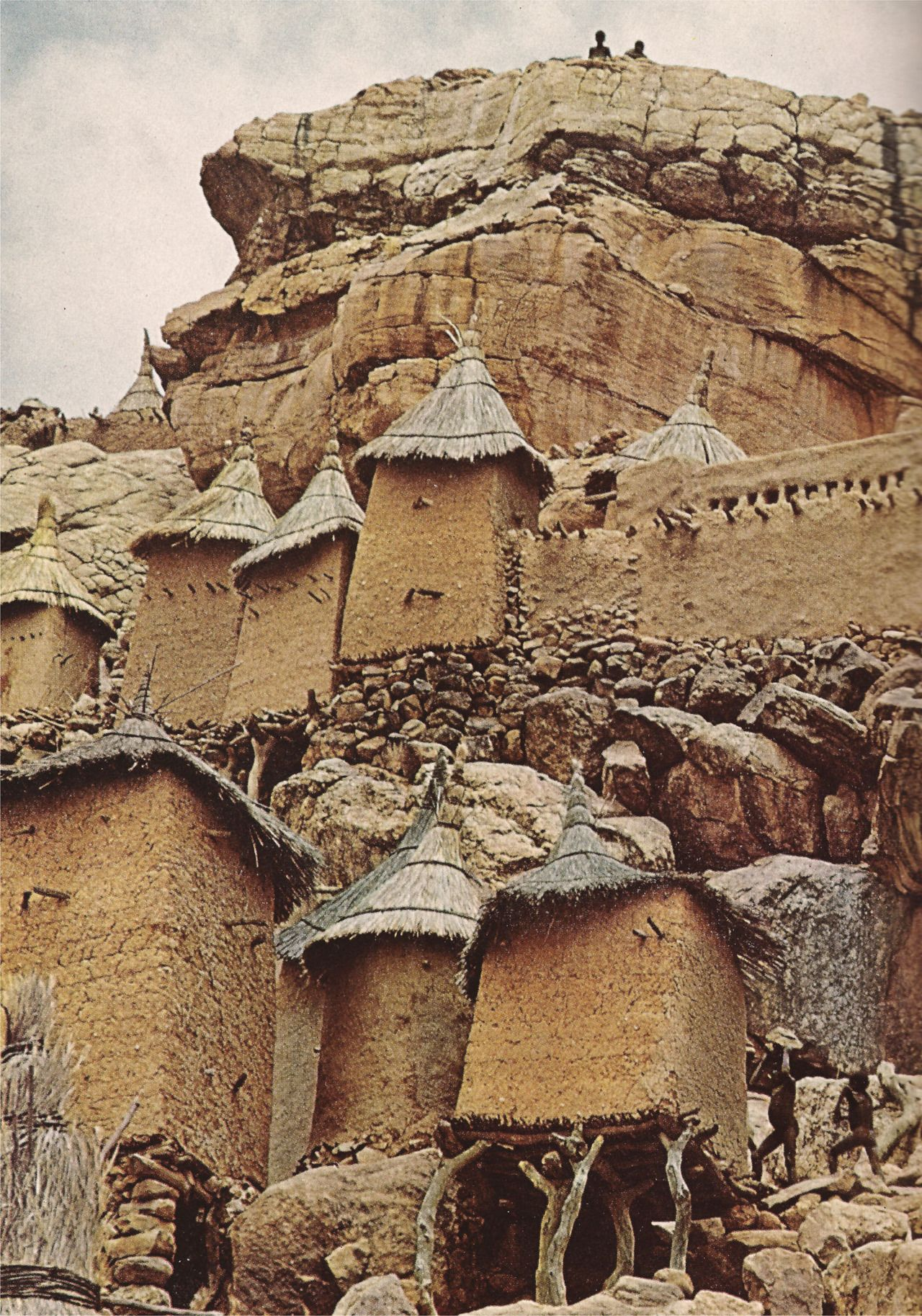 """""""Propped by rubble, logs, and faith, a family compound at Yenndouma, Mali, clings to a rock face."""" (National Geographic, 1969)"""