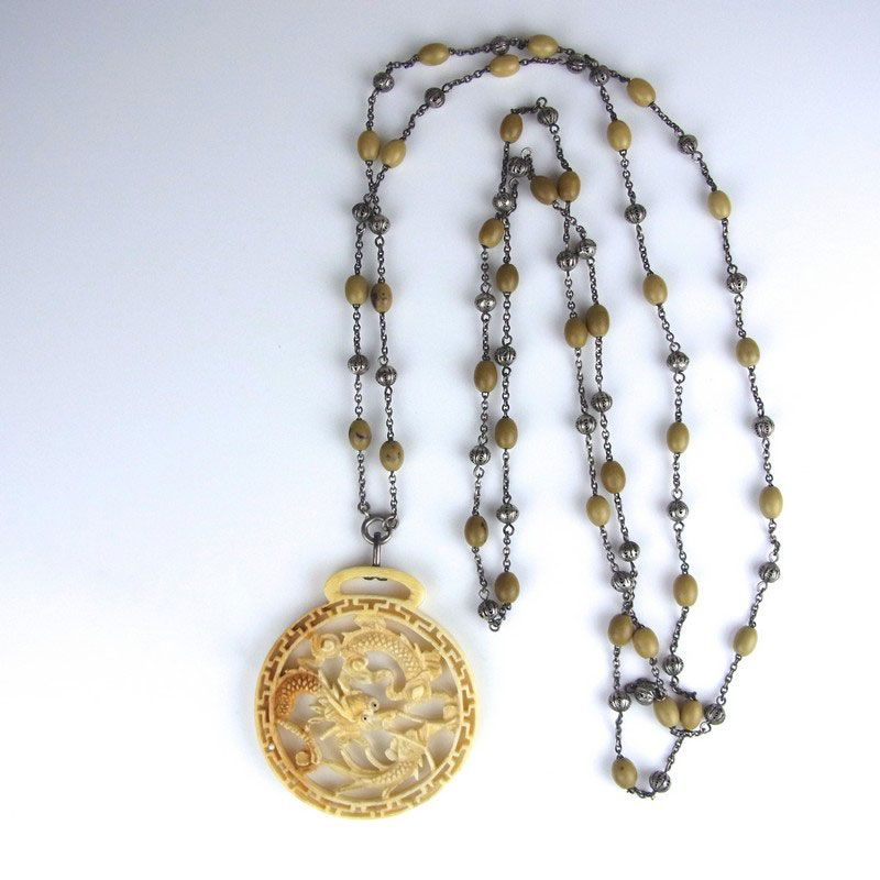 Cantonese ivory dragon pendant necklace. Cantonese ivory dragon pendant necklace. The ivory pendant depicting a Chinese dragon and hung from a silver necklace comprising small filigree balls and oval shaped beads. Pendant diameter 53 mm. Necklace length 1405 mm / 55.75 in. Total weight 37 grams.