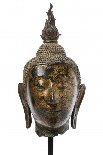 Siam, période d'Ayutthaya, XVIe siècle Tête de Bouddha en bronze ancienement laqué or, les cheveux surmontés de l'ushnisha et de la flamme, les oreilles aux longs lobes et les plis de beauté visibles à la naissance du cou. H. 25 cm