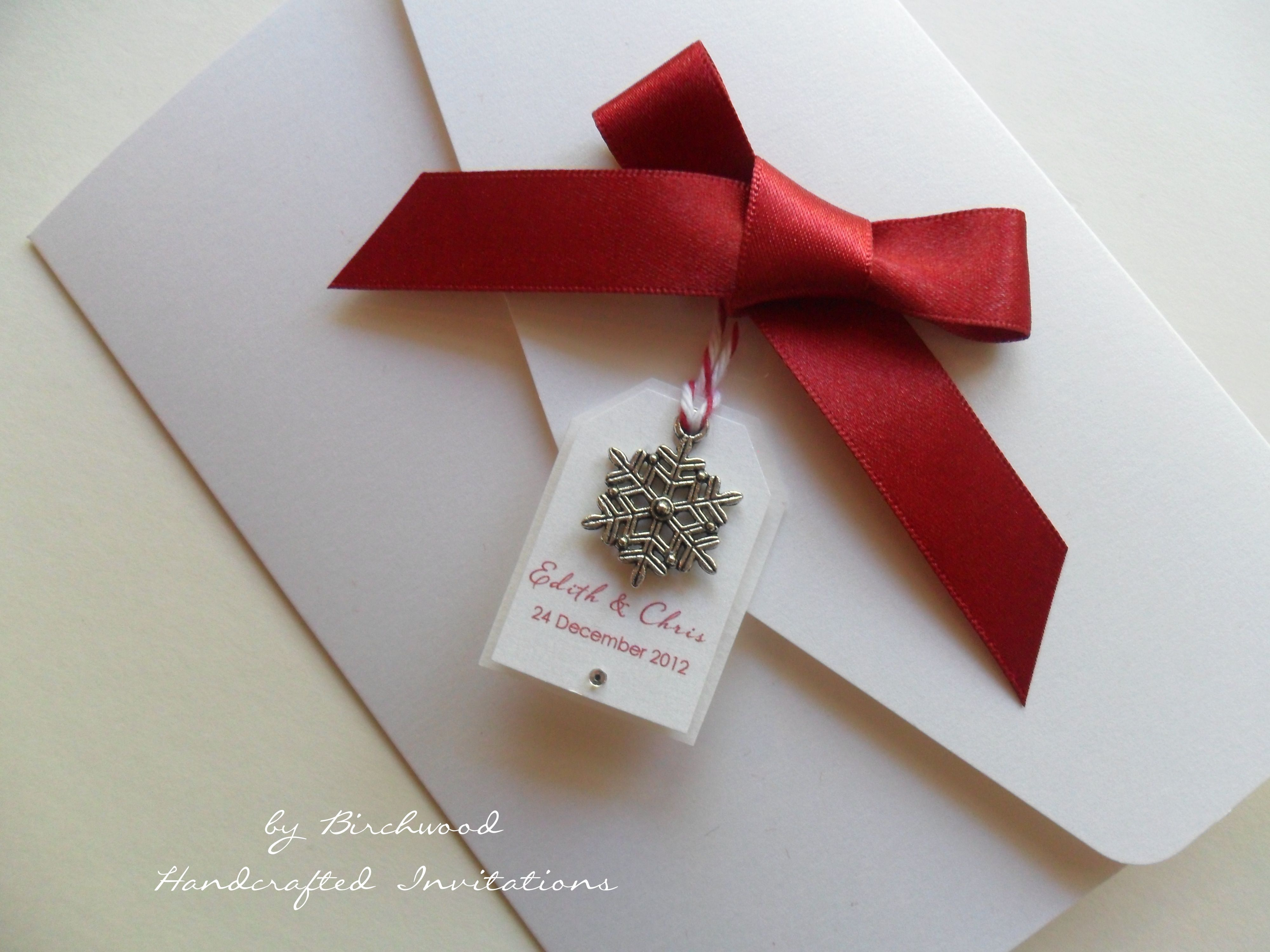 Winter themed wedding invitation with snowflake charm and satin red ...
