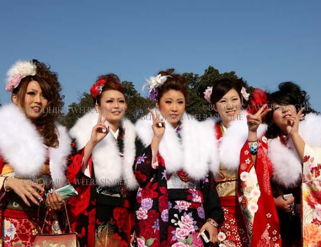 20-year-old Japanese women dressed in traditional kimonos pose for a picture during the Coming of Age Day at Cultural Hall on January 9, 2012 in Himeji, Japan. The event involves 20-year-old Japanese people celebrating their eligibility to drink alcohol, smoke and vote. (Photo by Buddhika Weerasinghe)