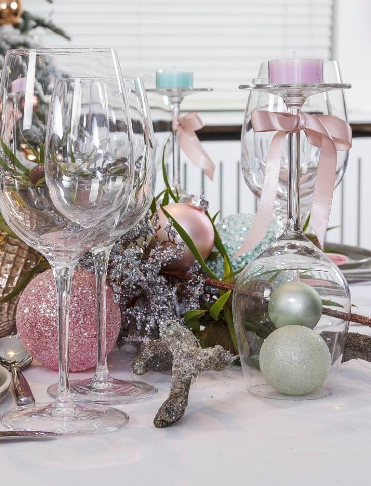 Wees inventief met het glaswerk op tafel. Draai een wijnglas om en gebruik deze als originele kandelaar. Steek er enkele kleine kerstballen onder en versier de hals met een strikje. Zet er nu een theelichtje op en branden maar!