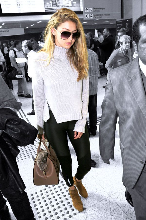 Gigi Hadid makes her way through the terminal in her trusty workout gear, played up by some high-end accessories.Gigi is wearing a Style Stalker sweater. #refinery29 http://www.refinery29.com/2015/06/88886/gigi-hadid-leggings-travel-outfit#slide-1