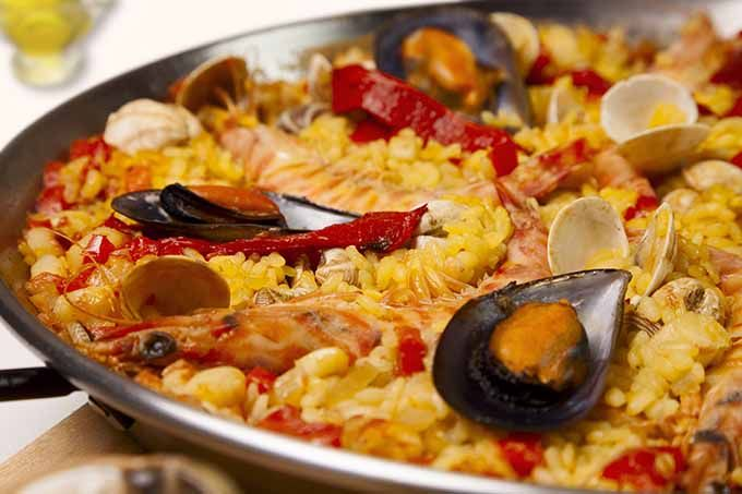 Comunidad Valenciana: la paella. Hay un ingrediente siempre presente: el arroz. La tradicional paella era una mezcla de arroz con alimentos que tenían a mano los labradores: pollo, conejo y hortalizas típicas de Valencia como el garrofón o la tabella.  La receta fue evolucionando y es usual encontrar, además de elementos de montaña,  complementos típicos del mar (como sepia o gambas). La opción clásica es degustarla en medio de la playa: por ejemplo en el restaurante La Pepica (Valencia).