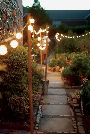 String lights on poles pushed into pots around the yard...could do the same with Shepard hooks or poles attached along the fence! Just such a pretty idea. Love it