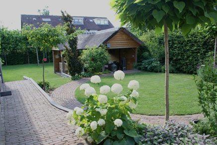 Het landelijke prieel met rieten kap is de absolute eyecatcher in deze tuin de l vorm van dit - Prieel tuin ...