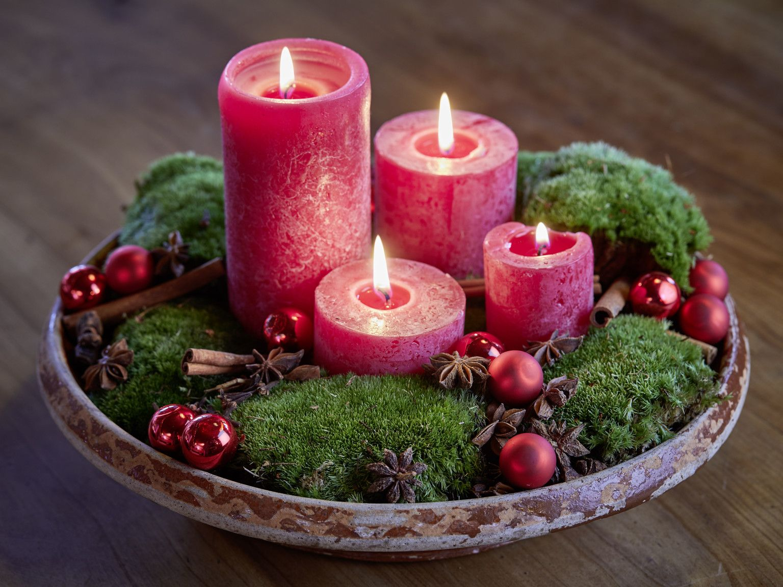 Photo of homemade advent wreath in bowl with moss, cinnamon sticks, star anise and tree …