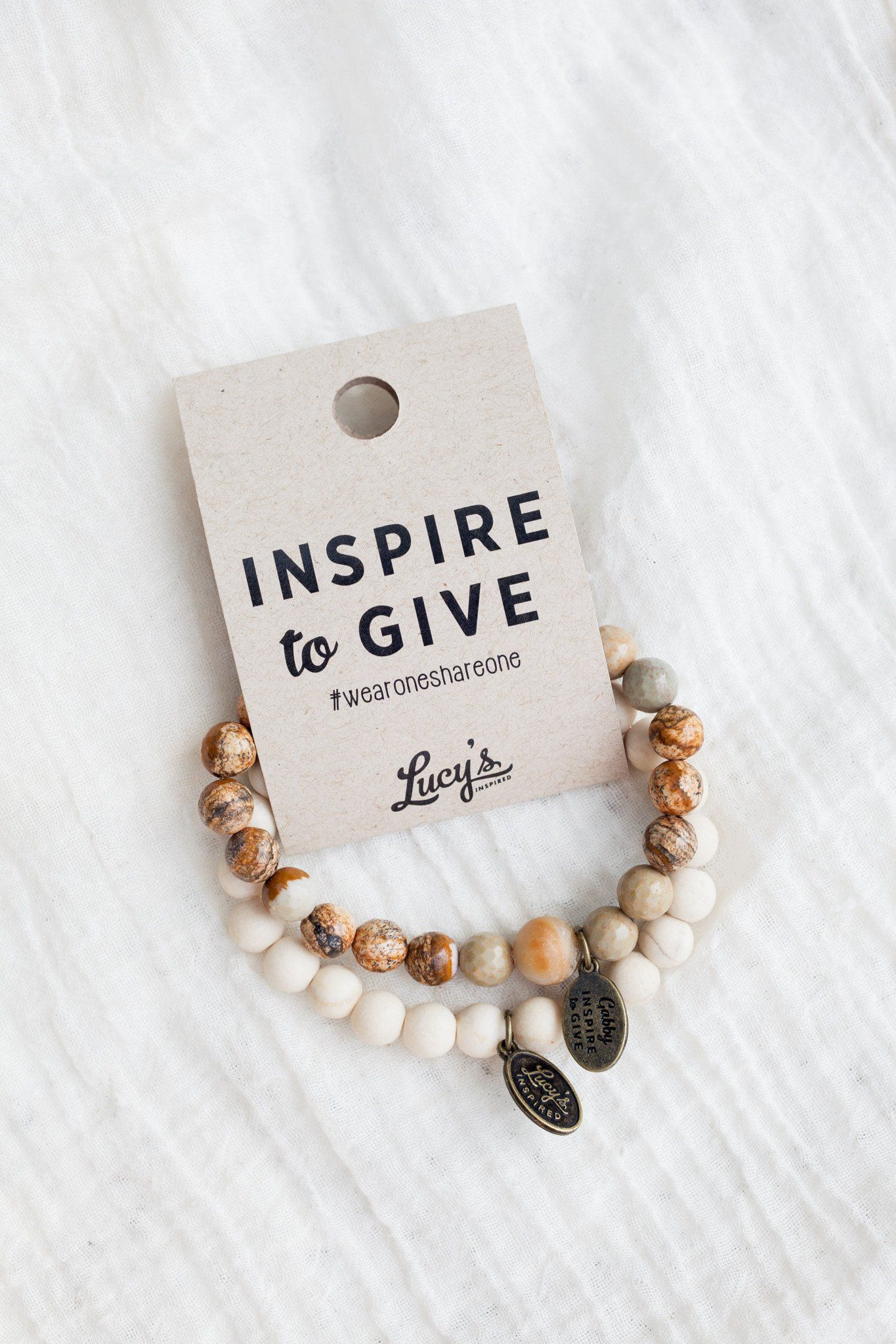 """Our Inspire to Give bracelet is two bracelets packaged together. Both bracelets are composed of small, varying colored beads. We have created these beautiful bracelets in honor of Gabriella Maria Menotti, affectionately called """"Gab Gab"""", who went to be with the Lord on December 20th, 2015 after a lifelong battle against a childhood disease. Her relentless dedication, paired with the support of her family, friends and caretakers, was an inspiration to everyone. Even though her time here was short"""