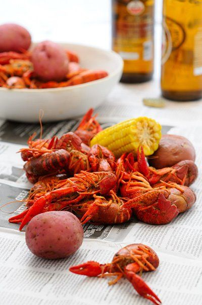 crawfish and potatoes with corn and beer on newspaper
