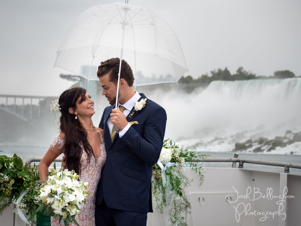 Cute Bride And Groom Laughing Wedding Ceremony Under Niagara Falls In The Rain With Umbrella