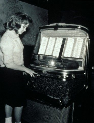 1950s teenage girl selecting music on coin-operated jukebox