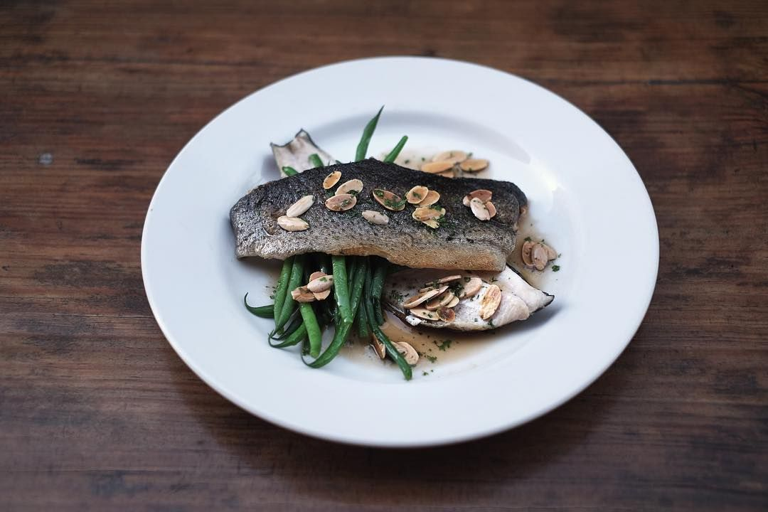 """Trout Amandine."" Boneless rainbow trout -- dredged in flour, pan-fried in browned butter, plated over sauteed green beans, garnished with toasted almonds."