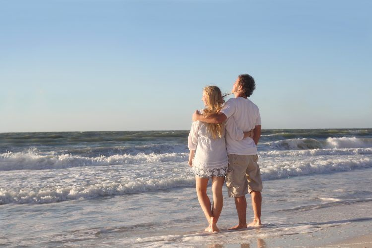 A happy young married couple stops to look at the ocean waves while walking with their arms around eachother along the white sand beach on a vacation.