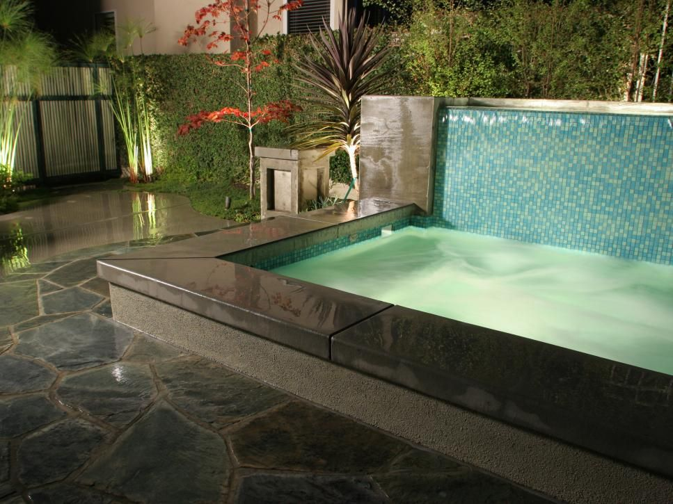 This luxurious outdoor hot tub incorporates a blue, teal and light ...