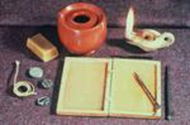 Writing materials used by Romas at various times. The hinged book was filled with wax (shown here as a separate item in ready to melt block form), which when hard could be written on with the elegant stylus; pen and inkpot are to hand for more durable writing, along with a lighted lamp, a spare wick and a seal.