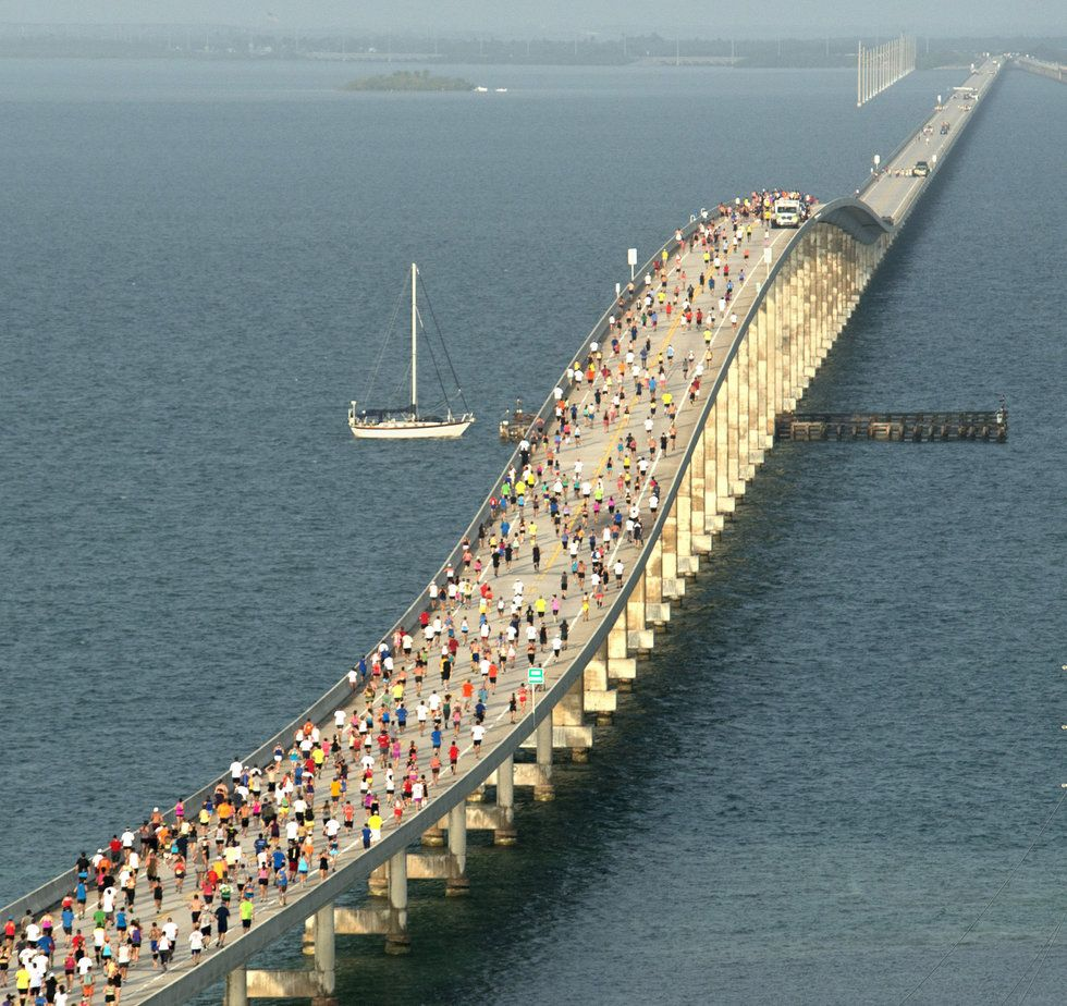 In this photo provided by the Florida Keys News Bureau, a sailboat readies to navigate under the Seven Mile Bridge in the Florida Keys as runners run over the span's highest 65-foot point during the 32nd Annual Seven Mile Bridge Run Saturday, April 13, 2013, near Marathon, Fla. Puente de las Siete Millas 16