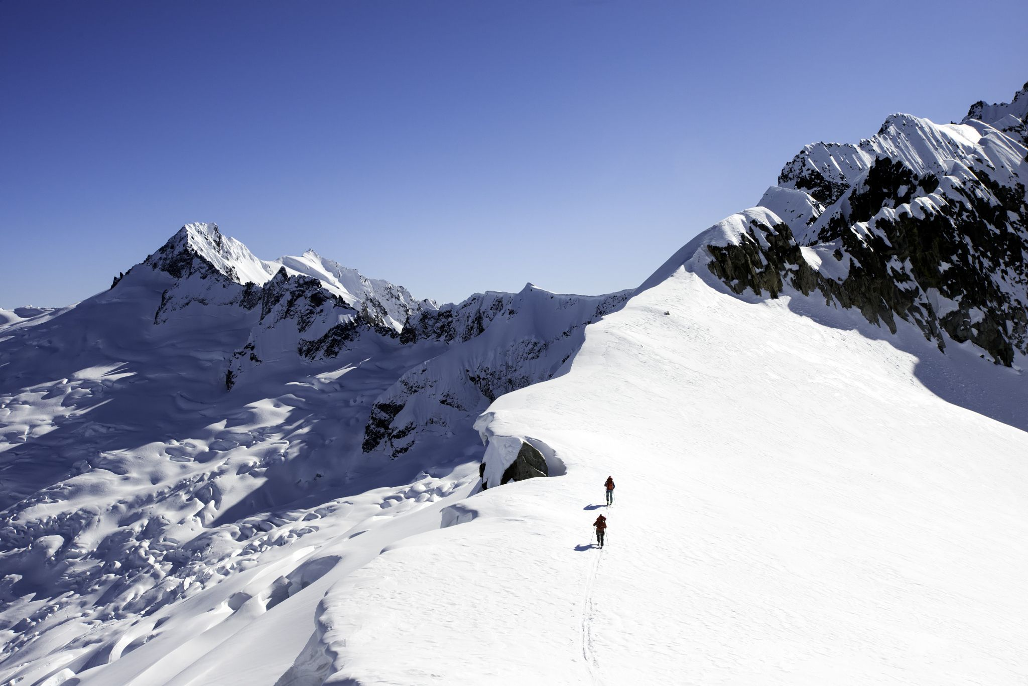 Skiing above the Boston Glacier - There are few glaciers in the North Cascades as wild as the Boston Glacier. Considered the widest ice field in the lower 48 states makes it big, but it is also a tumultuous place. Buckner and it's North Face rise in the background of this image and Andy and Mike Traslin skin up a ridge overlooking the expanse. This is the 'awesome' that makes the North Cascades so special.    Forbidden Tour, North Cascades, Washington, March 2015