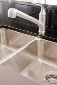clean a stainless sink with dish soap, baking soda, and lemon juice or baby oil