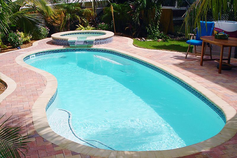 The Luau by Aloha Fiberglass Pools.  A classic kidney shaped pool with a fiberglass hot tub spilling into the pool.