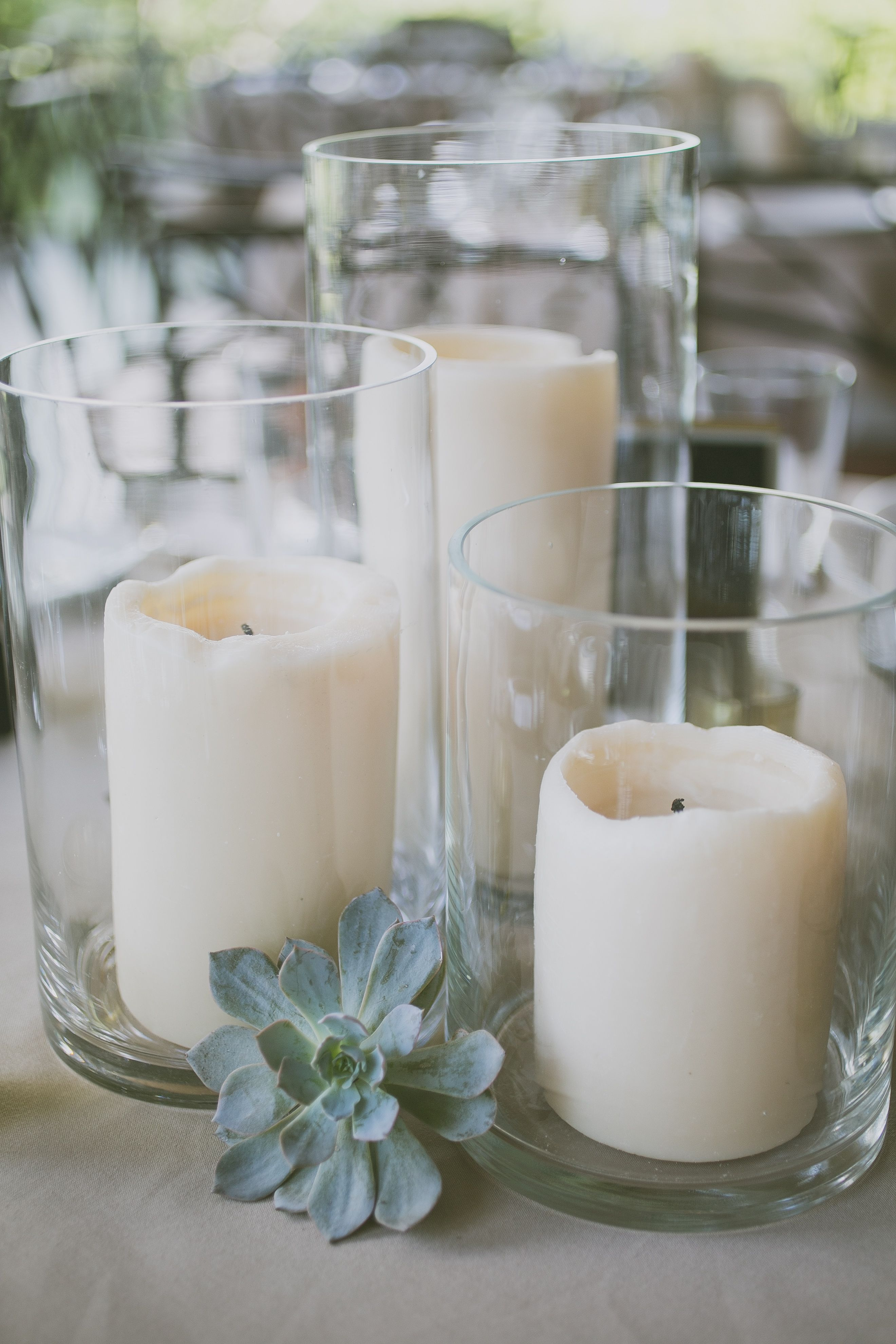 A trio of led pillar candles in vases with pale green